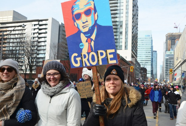 Toronto womens march and protest, women with a sign that is picture of Donald Trump in reds and blues with the word Grope written in large letters