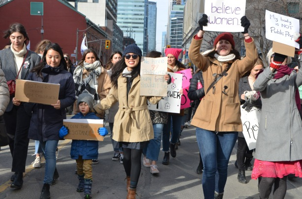 women walking down Bay st towards Nathan Phillips square and city hall, womens march