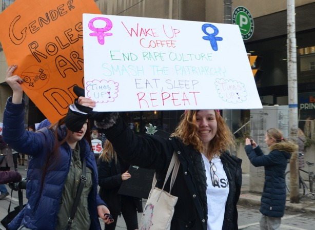 women holding protest sign, womens march, Toronto