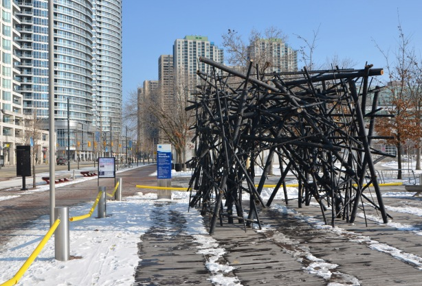 a tunnel like structure made of black bamboo poles loosely intertwined and joined together on the sidewalk beside Queens Quay, snow on the ground, condos in the background.