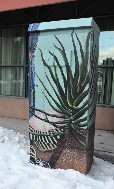 a metal telephone or traffic box on the sidewalk that has been painted with a picture of a cactus.
