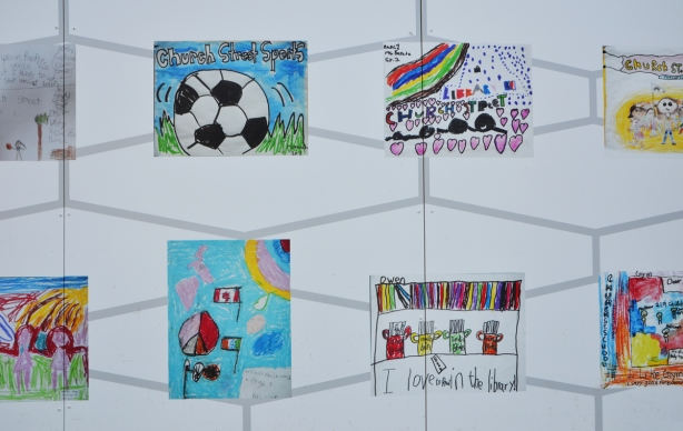 white construction hoardings with childrens paintings on it. a painting of a soccer ball, kids playing, words too