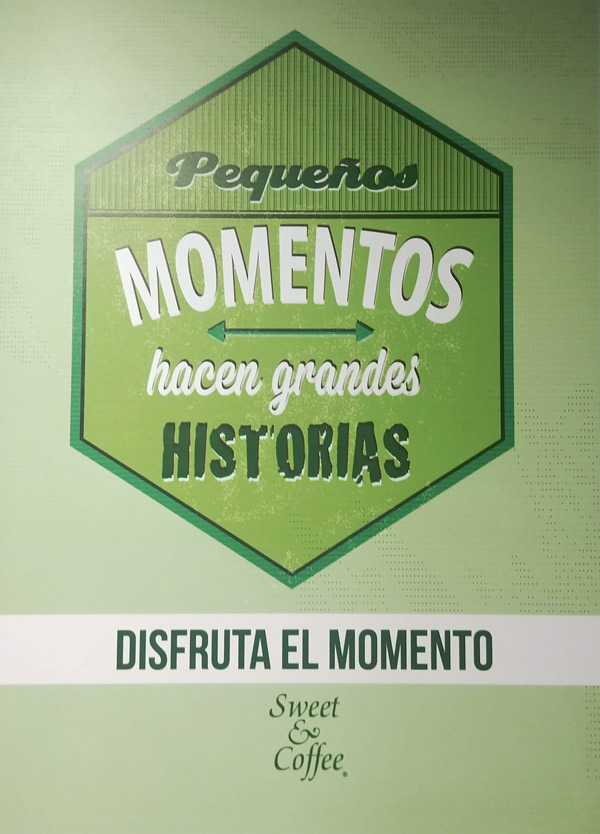 green and white poster hanging on a wall, words in spanish that say pequenos momentos hacen grandes historias, disfruta el momento which translates to small moments make great stories, enjoy the moment. It was in a Sweet and Coffee coffee shop in Ecuador.