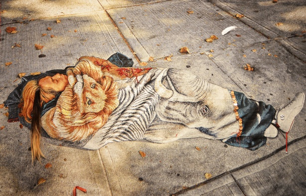 dream catcher by Rebecca Belmore, a large wall hanging of a person sleeping on the sidewalk, under a blanket with a picture of a lion on it.