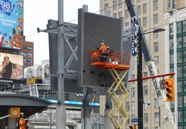 two men on a lift are working on a new elevated sign at Dundas square