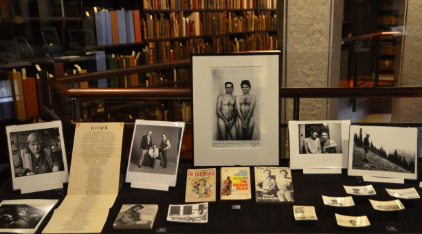 exhibit of photos by Allen Ginsberg displayed in the Thomas Fisher Rare Books Library at U of T, some black and white photos in a case, some books too, shelves of books in the background