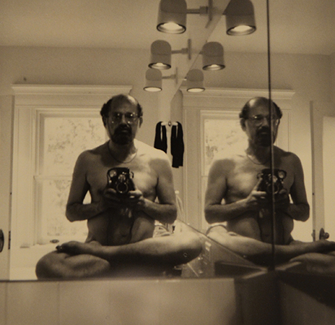 picture of a black and white photo taken by Allen Ginsberg of himself sitting naked and cross legged in front of a bathroom mirror
