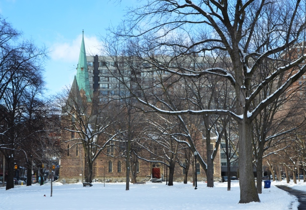 park, in winter, with large mature trees, in the background is Grace Church, brick building with green roofed steeple
