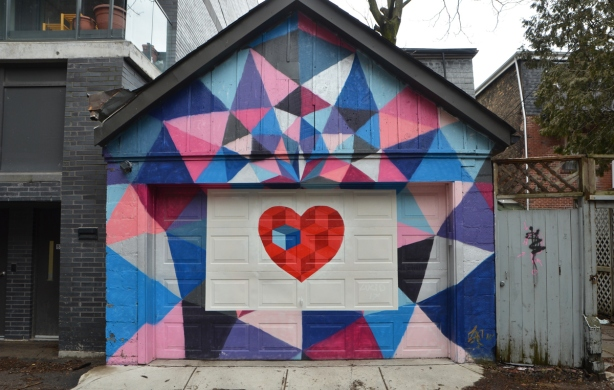the front of a garage is covered with street art. A bright red heart is in the middle from which coloured geometric shapes eminate outwards and cover the entire front of the building.