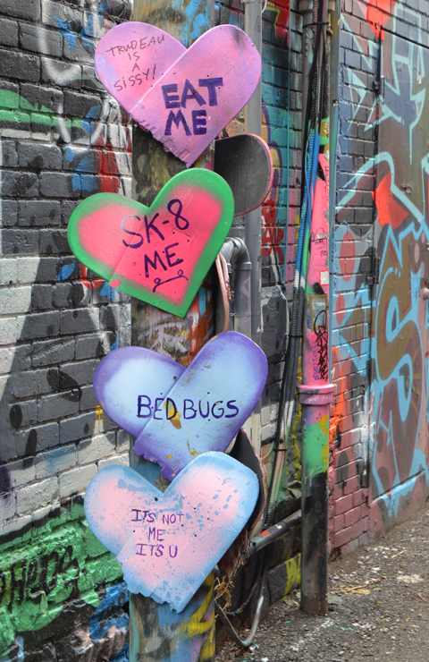on a utility pole in Graffiti alley, there are 4 paper hearts in pink and purple, with words written on them - bed bugs, sk8 me, its you not me,