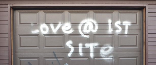 dark brown garage door,metal, with white spray paint words that say love @ first site