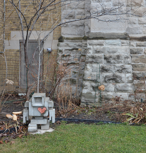 a small concrete love bot stands on the grass beside the garden in front of St. Patricks church, winter, no leaves on the small tree, stone church