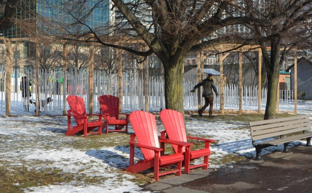 a man is touching and pushing a series of wind chimes that are part of an art installation at Toronto Music Garden as he walks by it. Snow covered ground, red muskoka chairs, park, large tree,