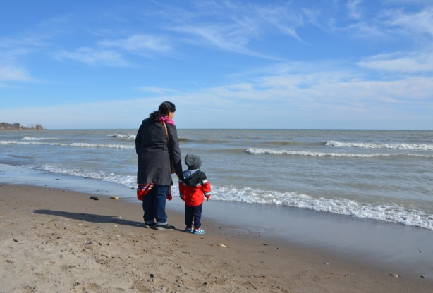 a mother holds her young son's hand as they stand together on a beach overlooking Lake Ontario, backs to the camera