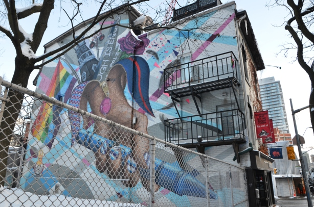 large mural on the side of a two storey building, with metal fire escapes on the side of the building as well. Mural is enough is enough, rainbow flag and other things