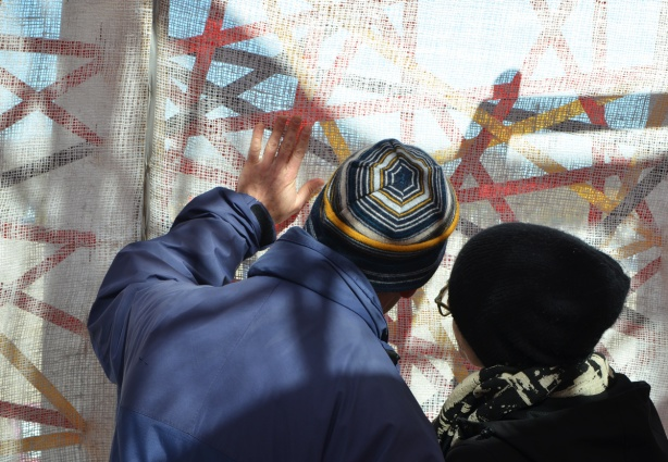 an older couple examine the fabric that is on the inside of Nest, a warming station at Kew Beach