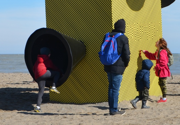 a child with a red jacket is trying to climb inside a large black speaker, conical shaped, on the side of a black and yellow art installation at the beach, warming stations, Kew Beach, lake ontario is in the background.