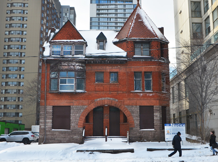 old, large, three storey red brick house with boarded up windows, about to be redeveloped, people walking past on the sidewalk, winter, street scene,