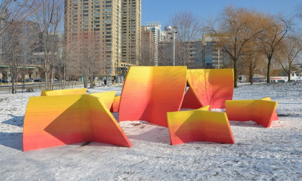 6 or 7 large wooden forms in convex and concave shapes in a snow covered park with highrises in the background. An art installation that is part of Ice Breakers 2018 on Toronto waterfront.