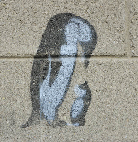small black and white stencil on a concrete block wall. An adult penguin is standing with its head bent over looking at a small black and white cat that is looking up at the penguin