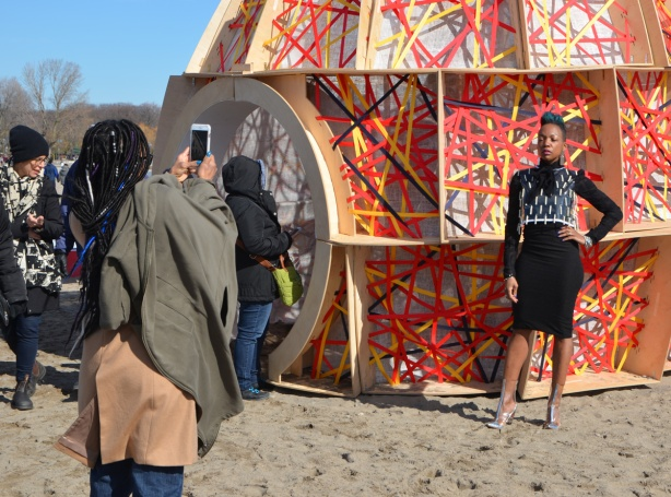 a woman model poses beside an art installation on the beach