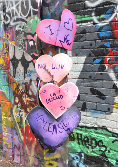 on a utility pole in Graffiti alley, there are 4 paper hearts in pink and purple, with words written on them - I love me, no luv,