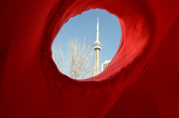 the CN tower with bright blue sky, as seen through the hole in a sculpture, the eye of a large red bear.