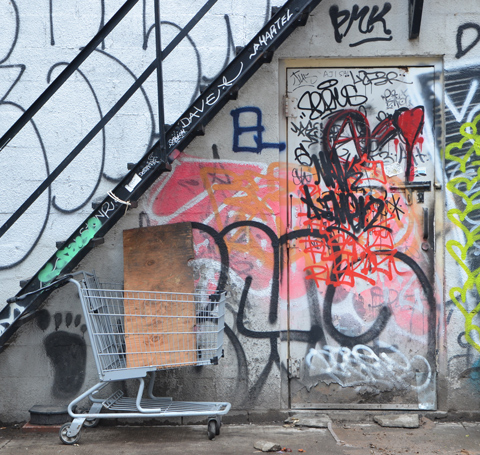 metal staircase, outside, running diagonally across the back of a building, a shopping cart under the stairs with a box in in, a door in the wall under the stairs, both door and wall are cover in graffiti including a large orange swath and a bright red heart