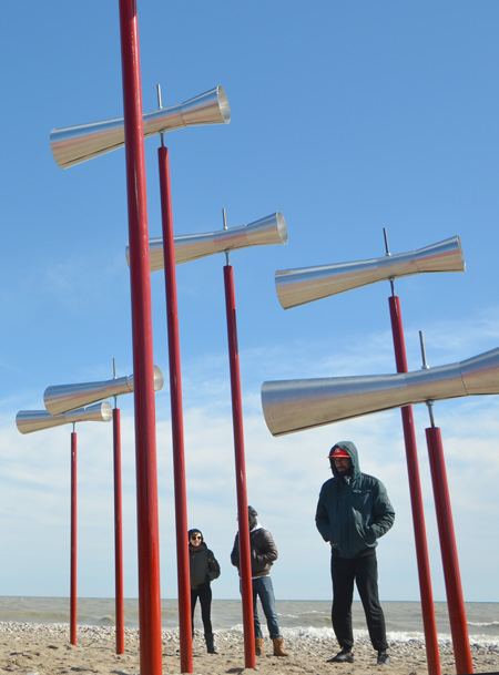 an art installation of small conical tubes like megaphones on red poles of differing heights, lake in background