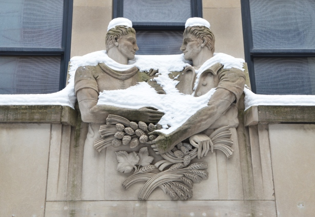 stone sculpture of the door of the Chang School at Ryerson, two men with interlocking arms, looking at each other, wheat, apples, and other produce in their hands, covered with snow