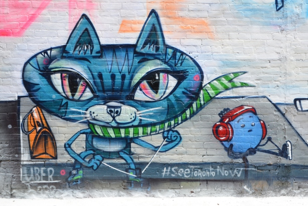 mural, painted, large blue cat with large head sitting beside an ice rink, with a little blue round character beside him who is wearing red ear muffs