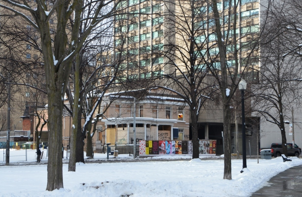 an older two storey house house boarded up with construction hoardings in front, looking at it through a park with large trees, winter