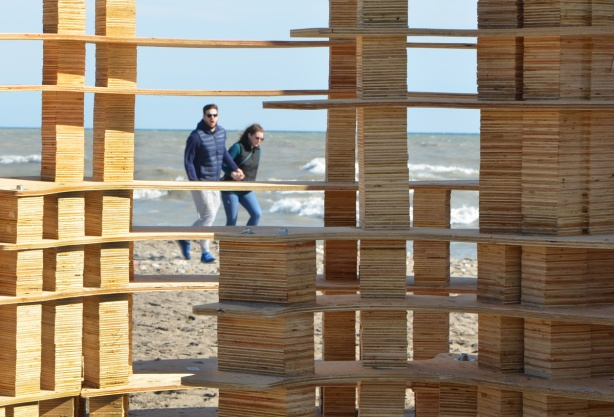 looking through part of rising up, a wood structure built on the beach, a couple walks hand in hand between the art installation and Lake Ontario