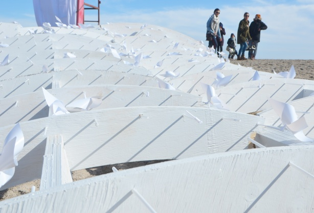 a few people in the background, they are looking at white wood and white plastic toy windmills lying on the ground. it is a collapsed art installation, part of warming stations at kew beach, by Lake Ontario
