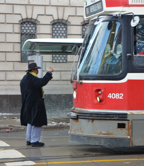 man in long coat and hat stands in front of a TTC street car with his arm up in the air.