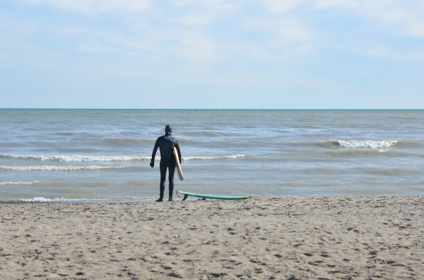 a lone person standing on a beach, looking out over Lake Ontario, back to camera, in full wetsuit, holding onto a surf board under his (or her) arm, another surfboard sits on the sand.