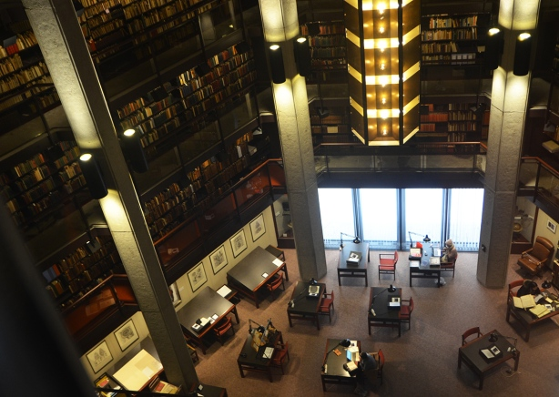 interior of Thomas Fisher Rare Book library, looking down from the upper level to the tables below. Shelves of books line all the walls, ceiling is open to 4 or 5 storeys up , large central light fixture