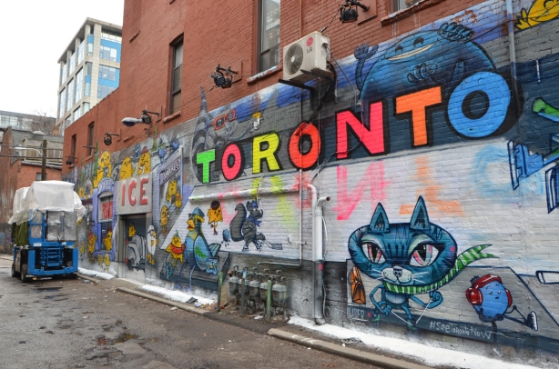 most of a new mural by uber5000 in Graffiti Alley based on winter activities at Nathan Phillips Square