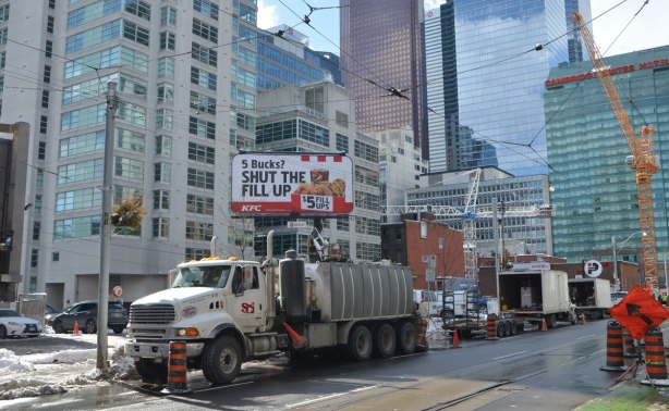 large truck parked on a street with tall buildings behind, and a large billboard with a KFC ad on it