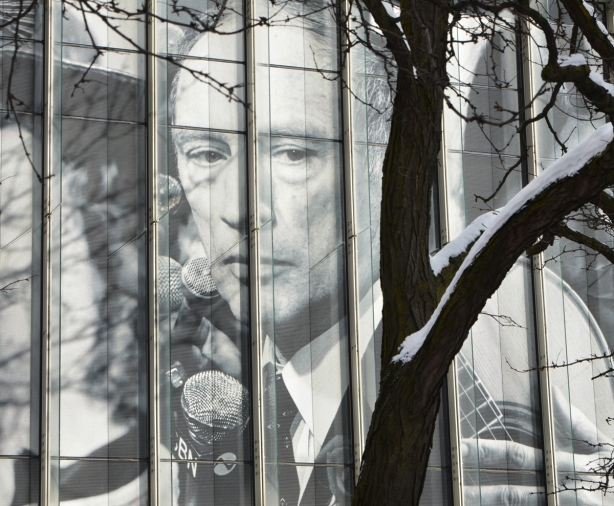 a large black and white picture of Pierre Elliott Trudeau in the window of the Ryerson Image Center, with a tree in front of it, some snow on the tree
