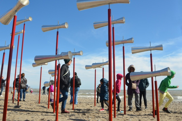 people walking amongst an an art installation of small conical tubes like megaphones on red poles of differing heights.