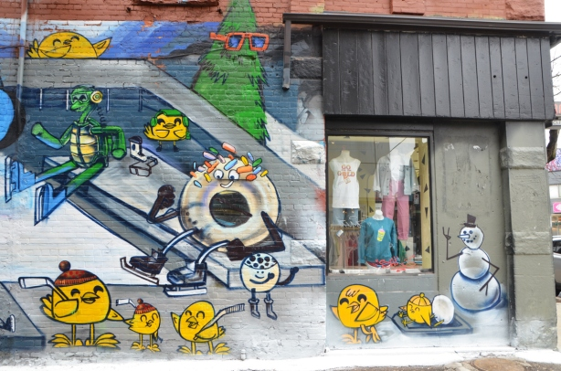 right hand side of a large mural by uber5000 in Graffiti alley, with shop window in the picture.  Theme of the mural is skating at Nathan Phillips square in toronto.  little yellow birdies, a green frog is puttin on skates as is a donut with white frosting and a few sprinkles