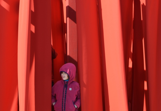 a girl in pink jacket with pink hood stands between large flaps of red fabric that is part of Obstacles, an art installation
