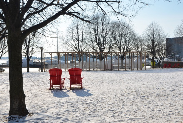 the back side of two red muskoka chairs in a snow covered park with a large art installation of wind chimes in the background
