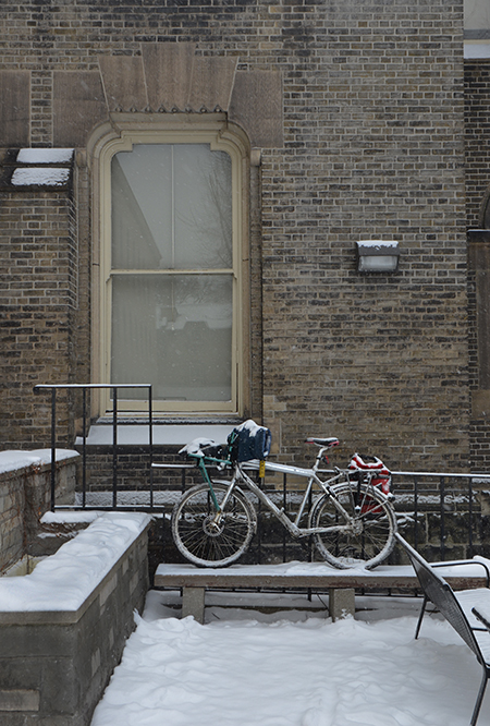 a bike parked outside an old brick building on St. George campus of U of T, snow covered