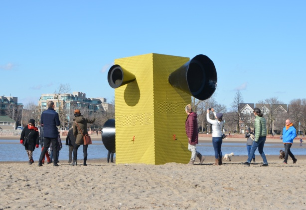 people on the beach checking out the art installation, Make Some Noise, a large yellow and black vertical box, with four large black loudspeakers