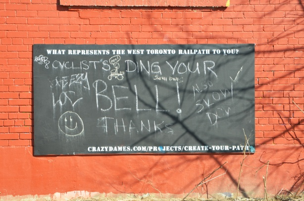 large chalkboard on an orange brick wall with notes to tell cyclists to slow down and ring their bells.