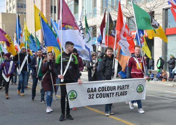 A group of young people walking in the St. Patricks day parade, holding a banner and everyone is holding a flag from a Irish county. GAA Colour Party, 32 county flags.