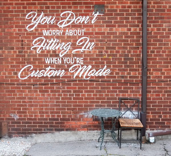 a amll metal table and a chair outside, against a brick wall. On the wall, in white paint, are the words You Don't worry about fitting in when you're Custom Made