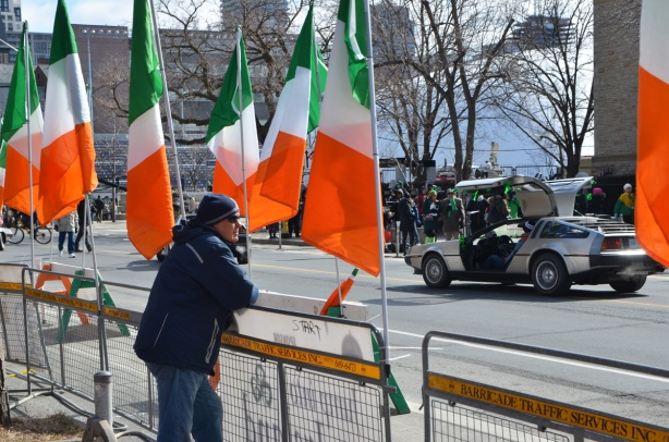 a man stands on a sidewalk, leaning on a barricade, lots of large Irish flags, a delorean car with its door open is across the street